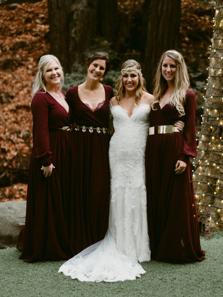 The bride was wearing a strapless lace dress with a train, and the bridesmaids rocked burgundy dresses with different belts