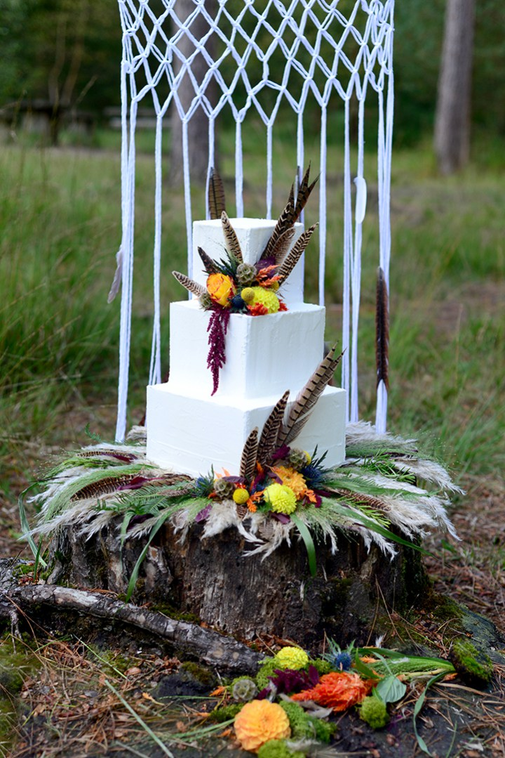 The wedding cake is a square one, with feathers and bold autumn flowers