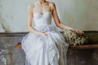 02 a spaghetti strap gown with a corset bodice and a tulle skirt, an updo with with flowers