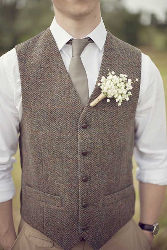 a tweed vest, a white shirt and a grey tie with a rustic baby's breath boutonniere