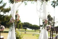 02 country chic wedding arch with white fabric and pink flowers