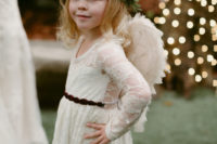 03 The darling flower girl is wearing a lace dress from Posh Peanut Kids and feather angel wings