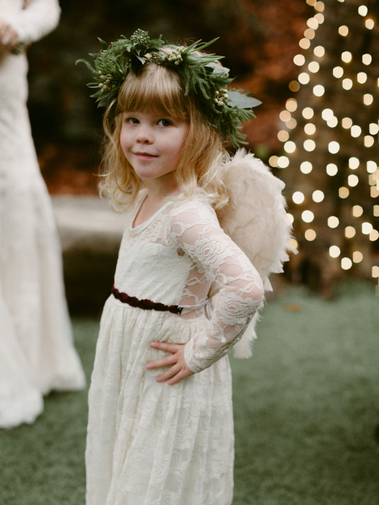 The darling flower girl is wearing a lace dress from Posh Peanut Kids and feather angel wings