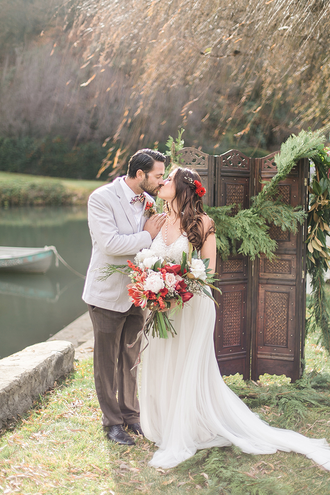 The wedding backdrop is a wooden one, decorated with evergreens for a rustic feel