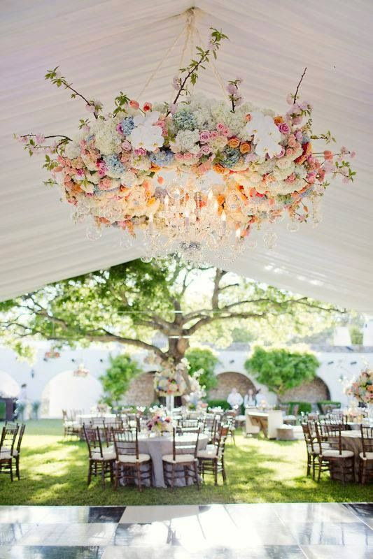large chandelier with pink and peach flowers and ivory and white shades over the dance floor