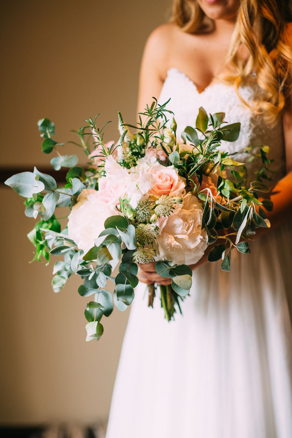 As blush peonies and roses are favorite bride's flowers, they were chosen for her bouquet and florals