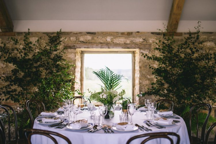 Neutral decor was spruced up with greenery, ferns and white flowers