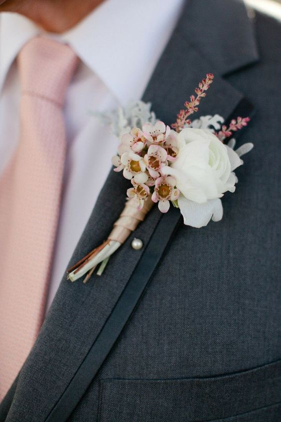 dark grey suit, a pink tie and fresh flower boutonniere