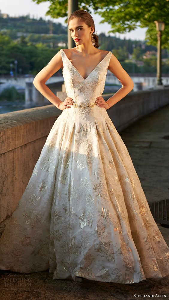 sleeveless V neck ball gown with gold appliques and a belt