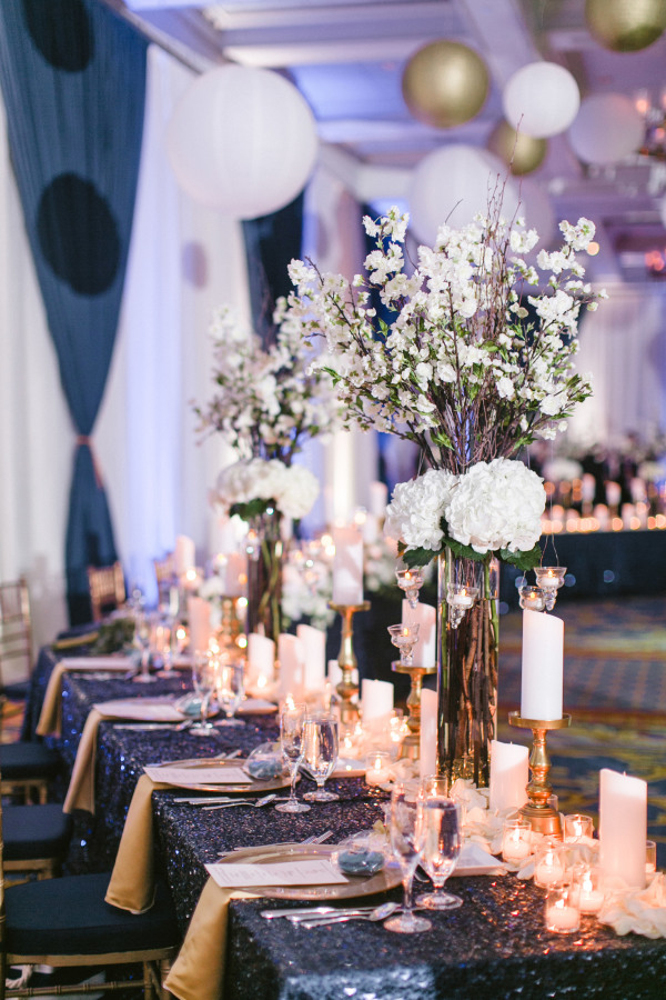 Navy sequin tablecloths, candles and white florals look very elegant