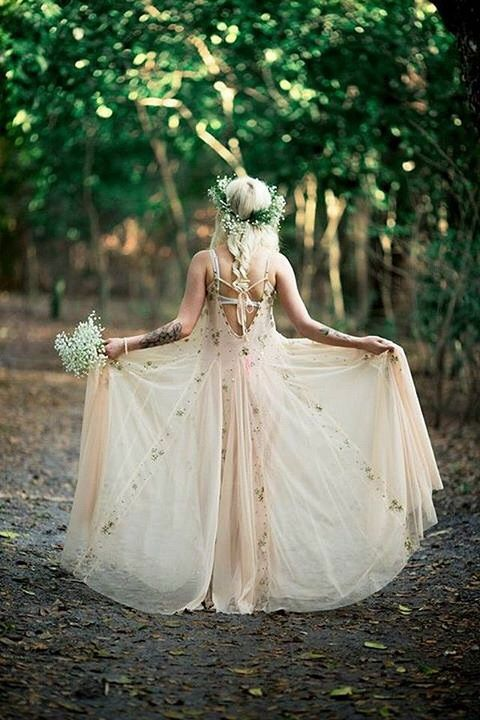ethereal wedding dress in blush with floral patterns and a greenery crown