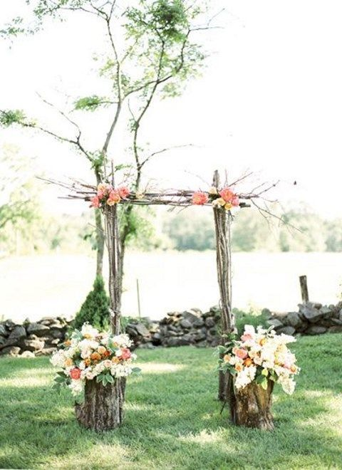 outdoor rustic wedding arch with fresh flowers