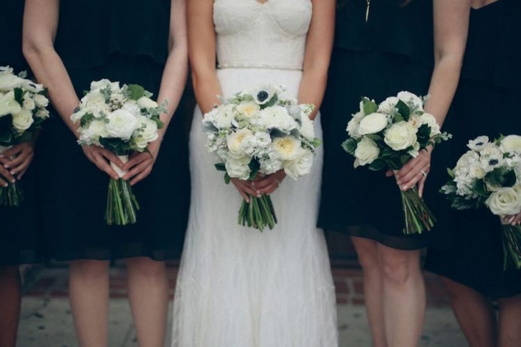 the bridesmaids were dressed in black with white bouquets for a chic look