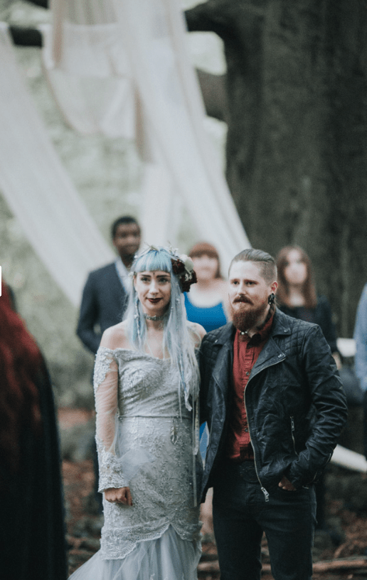 The bride had a lace blue off the shoulder dress and blue hair, the groom rocked a leather jacket