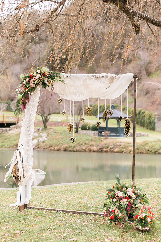 The wedding arch was made of wood and decorated with wwhite tulle, giant pinecones and lush holiday florals