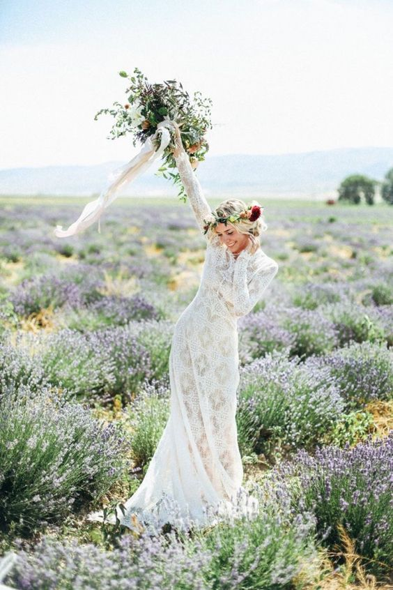 lace wedding dress with long sleeves, a floral crown and a messy bouquet