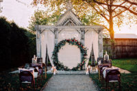 07 This gorgeous oversized wreath backdrop of greenery and flowers looks unforgettable