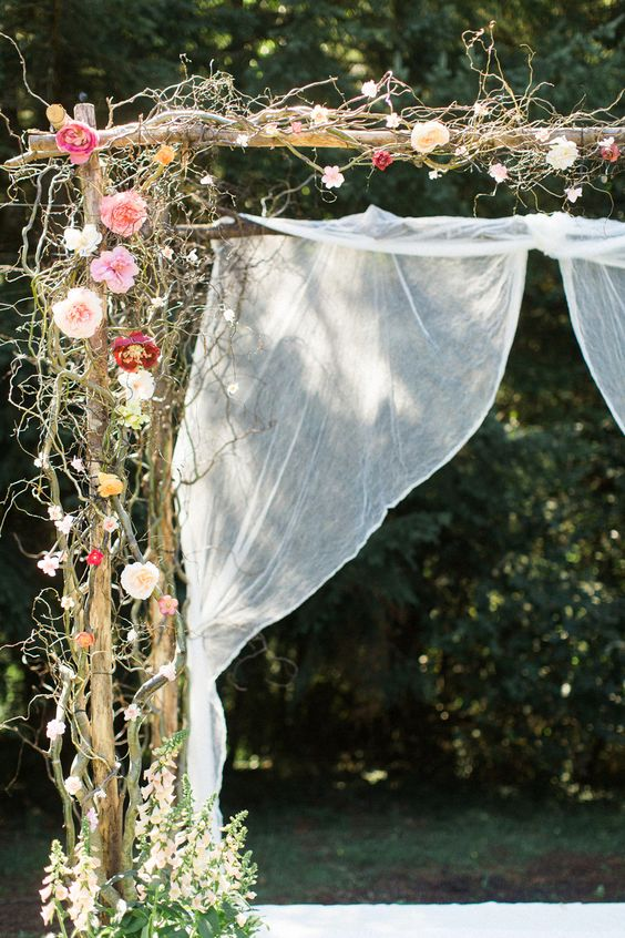wooden arch with vine and flowers, flowy fabric