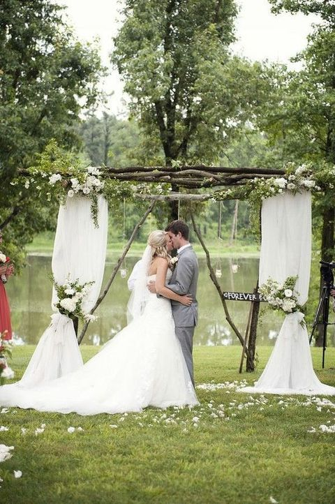 wooden wedding arch with flowy fabric and white flowers