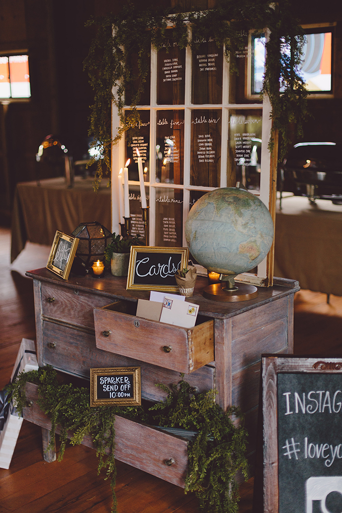 The barn was decorated in vintage style, with greenery, moss, an old window seating chart and candles