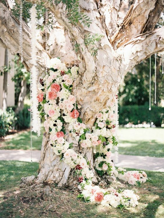 a large tree covered with pastel and neutral flowers and crystals