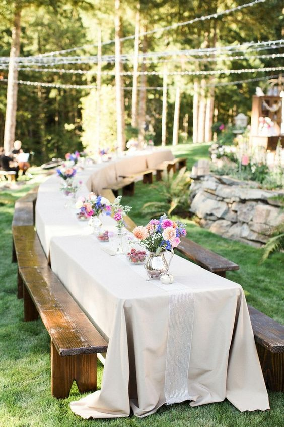 backyard tables with colorful flower centerpieces and benches