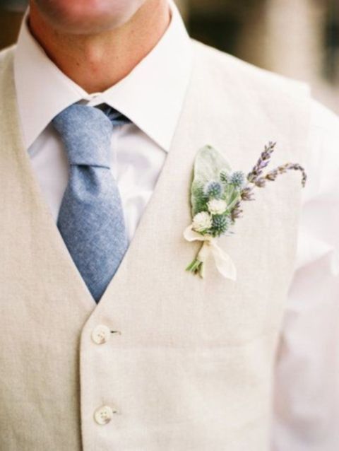 beige vest, a white shirt and a blue tie