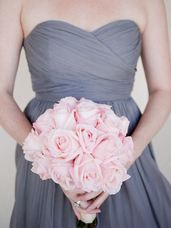 draped grey bridesmaid's dress and a pink rose bouquet