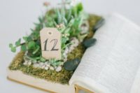 11 an old book centerpiece with succulents and greenery and a table number