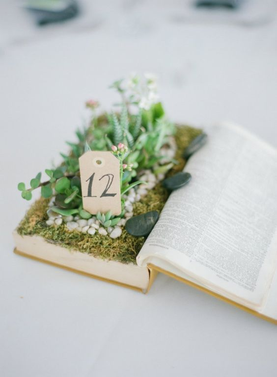 an old book centerpiece with succulents and greenery and a table number