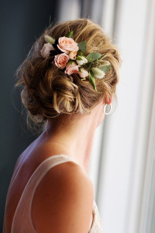 a curled updo with a fresh flower accent