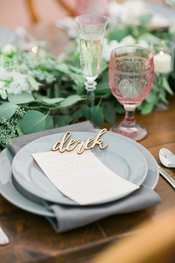 elegant place setting with grey plates and a greenery table runner