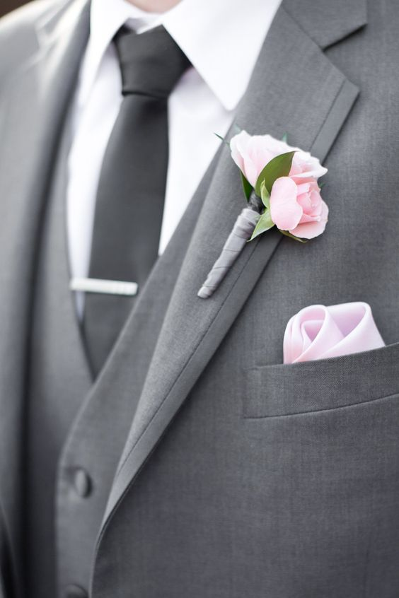 grey groom suit with a black tie and a pink boutonniere