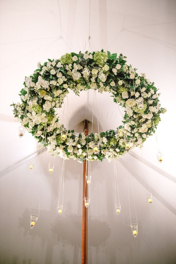 white roses and greenery chandelier with hanging candle holders