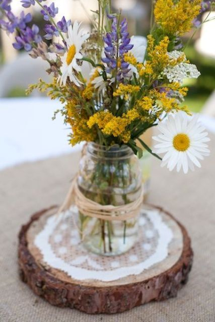 a cool centerpiece with purple, yellow and white wildflowers on a wooden slice