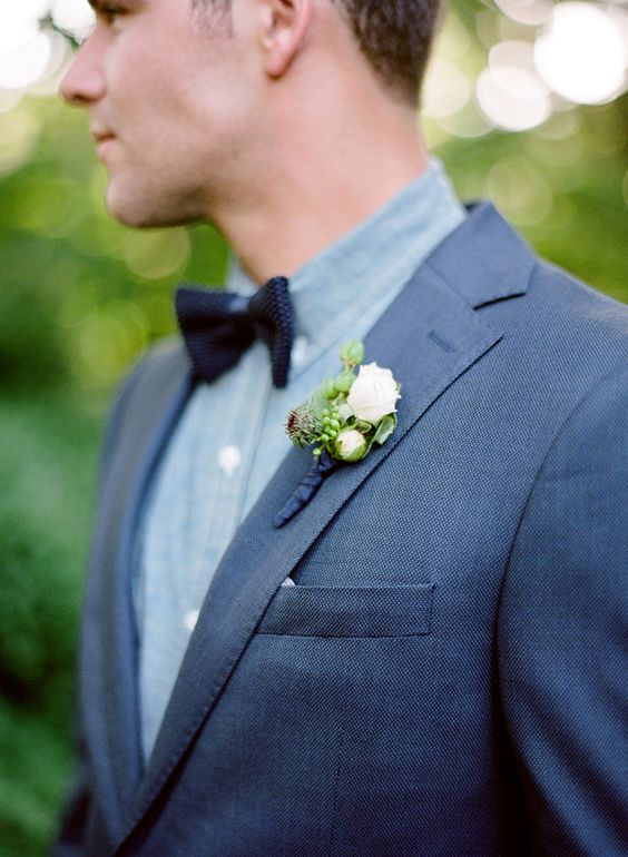blue suit, a grey shirt and a navy bow tie