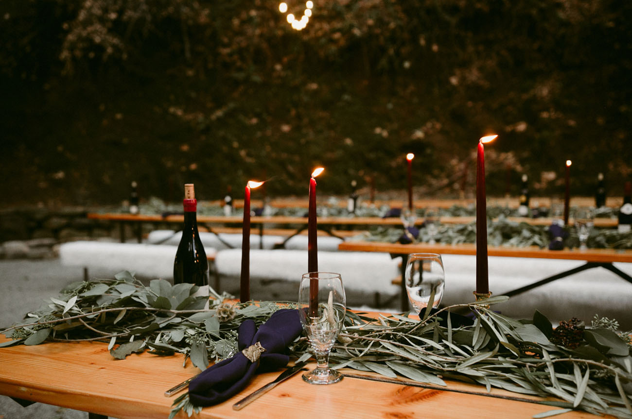 Fresh greenery runners, navy napkins and burgundy candles looked magical