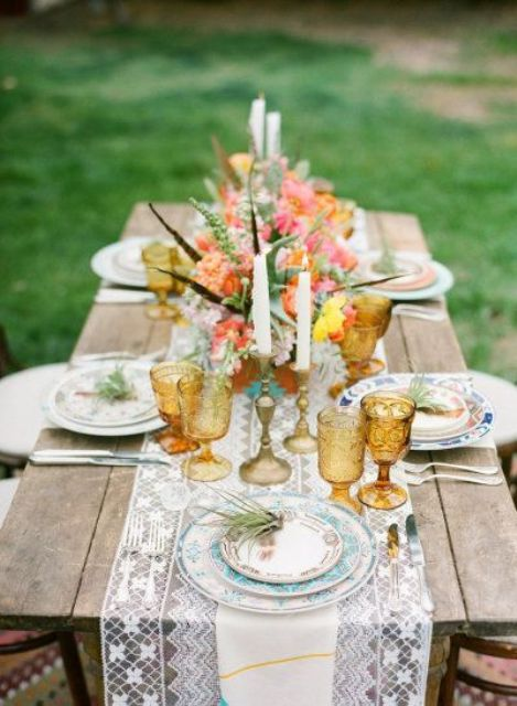 a lace table runner, tanned glassware, feathers and flowers