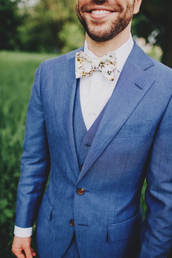 blue suit, a vest and a whimsy floral bow tie