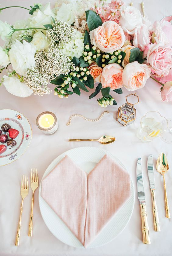 blush table setting spruced up with gold cutlery looks very romantic