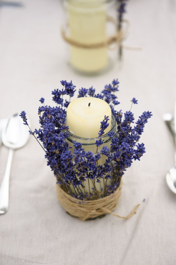 a jar with a pillar candle wrapped with lavender and twine