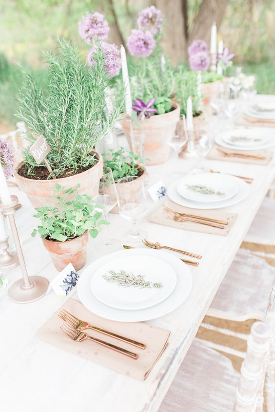 herb centerpieces and purple flowers as a living table runner
