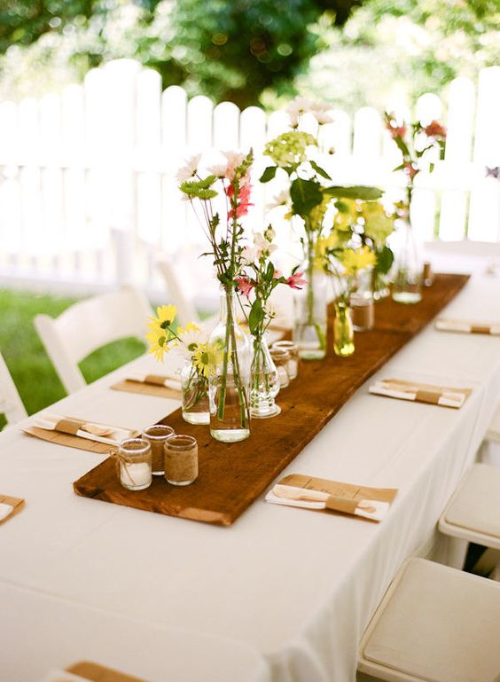 spring table setting with a wooden board, candles and flowers on it