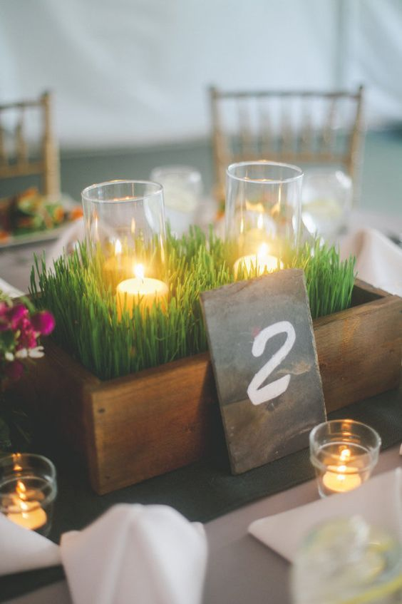 a box with wheatgrass and candles is a nice and fresh spring centerpiece