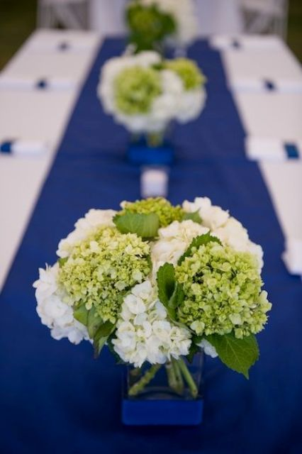 greenery and white hydrangeas on a bold blue table runner