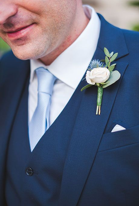 navy suit with a vest, a white shirt and a light blue tie