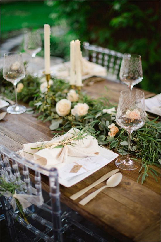 rustic wood table with a greenery and flower swag runner
