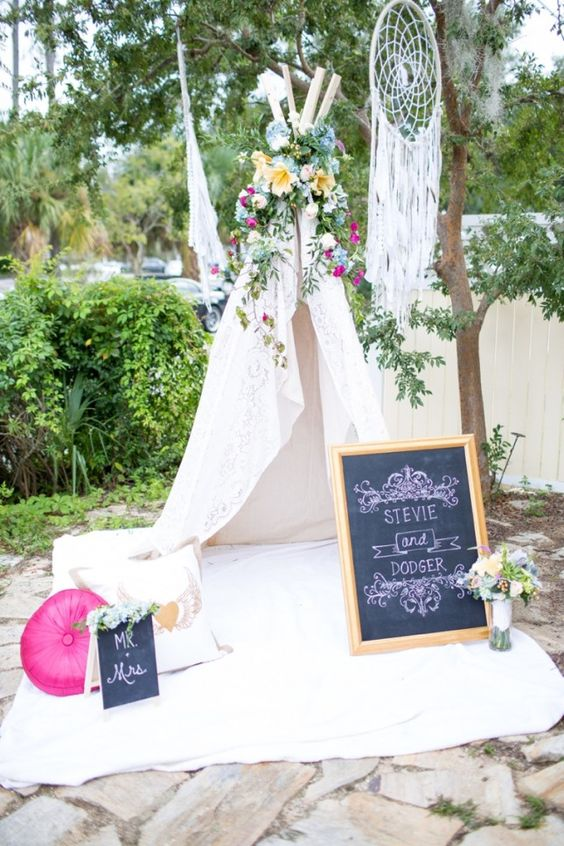 a teepee topped with bold flowers, a dream catcher