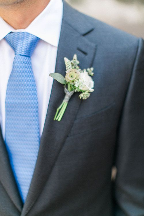 slate grey suit, a bold blue tie and a boutonniere