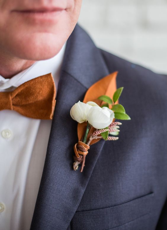 dark grey suit, a copper bow tie and a copper and white boutonniere